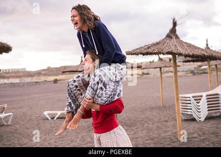 Couple sur la plage ludique. le jeune homme, la jeune fille sur son épaule et tous deux beaucoup rire comme un fou. journée de vacances pour jeunes et belles p Banque D'Images