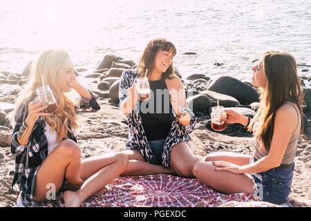 Groupe de femelles amis assis et profiter de l'activité de loisirs pendant les vacances d'été à la plage près de l'océan. Les sourires et les personnes gaies ha Banque D'Images