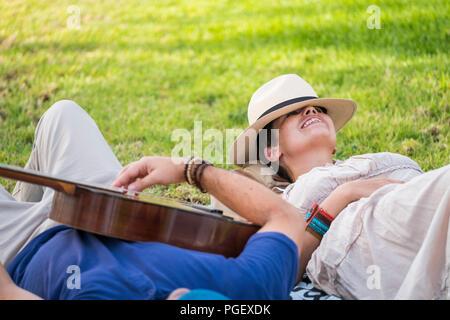 Heureux et détendu cheerful couple allongé sur l'herbe naturelle et profiter de l'activité de loisirs de plein air avec un beau temps à la saison du printemps. man pl Banque D'Images
