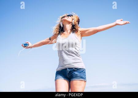 Attrayant beau joyeux caucasian middle age woman smiling at the beach in tropical place tandis que écouter de la musique avec le téléphone intelligent. personnes enjoyi Banque D'Images