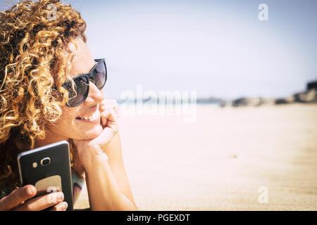 Joyeuse et attrayante jeune femme se coucha sur le sable blanc de la plage de paradise resort vacationo et profiter de la maison de vacances. Utilisez la fonction téléphone pour rester