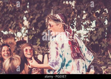 Jeune femme blonde crazy et les filles dans l'amitié tous ensemble célébrer et s'amuser dans un lieu naturel bio. sourires et rires pour groupe d'Hipp Banque D'Images