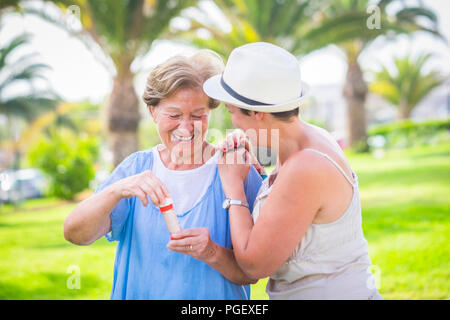 Deux âges différents comme mère et fille jouer ensemble dans l'activité de loisirs de plein air avec des bulles de savon. profiter de la journée dans le parc avec plante verte Banque D'Images