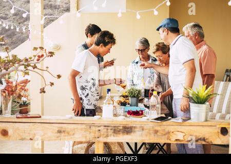 Groupe de gens différents âges de maturité jeune pour avoir du plaisir ensemble manger de la nourriture et de boire à l'amitié à la piscine en plein air sur la terrasse. Banque D'Images