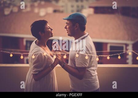 Beau moyen age couple in love smiling eachother et à la recherche dans les yeux à la terrasse avec une vue de dessus. houese relation Banque D'Images