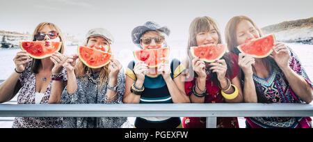 Groupe de nice cute cheerful young women friends rester ensemble s'amuser et profiter de l'amitié prendre une pastèque rouge près de l'expression de visage. Banque D'Images