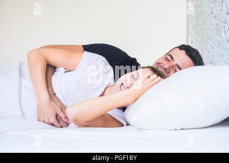 Happy young couple allongé et dormir ou se réveiller le matin tôt à la maison. Chambre blanche à la maison et les personnes serrant avec amour et relationshi