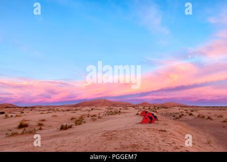 Camping dans le désert du Sahara au Maroc. Une rangée de petites tentes rouges sous un soleil coloré. Thème d'aventure.