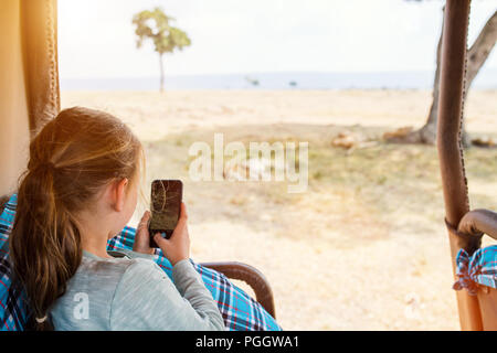 Adorable petite fille au Kenya safari sur commande de jeu de matin en véhicule découvert en observant les lions Banque D'Images