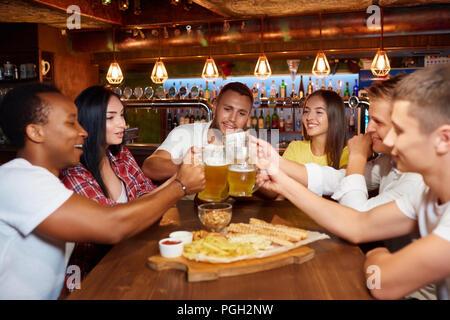 Groupe international d'amis fête avec des toasts et des verres de bière avec clink. Beaux jeunes gens de s'amuser ensemble, la cl de bière Banque D'Images