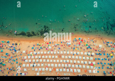 Vue de dessus de l'antenne sur la plage. Les gens, les parapluies, le sable et les vagues