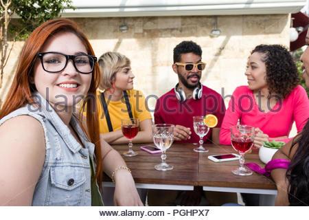 Professionnels de la génération Y et d'encouragement d'amis boire ensemble au café bar piscine. Mixed Race groupe d'amis s'amuser au restaurant à l'extérieur. Printemps, wa Banque D'Images