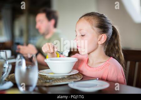 Adorable petite fille qui mange son petit-déjeuner à la maison ou au restaurant Banque D'Images
