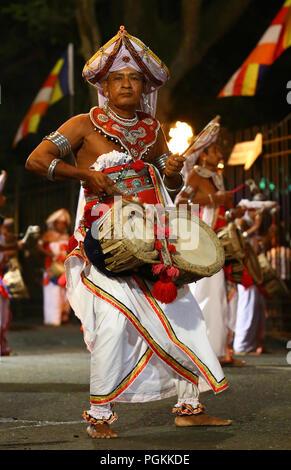 Le Sri Lanka. Août 25, 2018. Un danseur traditionnel du Sri Lanka joue la musique traditionnelle et se produit devant le Temple Bouddhiste historique de la dent, qu'il prend part à une procession au cours de l'Esala Perahera festival à l'ancienne capitale de la colline de Kandy, quelques 116 km de Colombo le 25 août 2018. Le festival comporte un cortège de nuit, danseurs de Kandy aménagés, incendie des musiciens traditionnels, les artistes interprètes ou exécutants et les éléphants incendie acrobatique, rassemblant des milliers de touristes et des spectateurs de partout dans l'île. Credit: Pradeep Dambarage/Pacific Press/Alamy Live News Banque D'Images