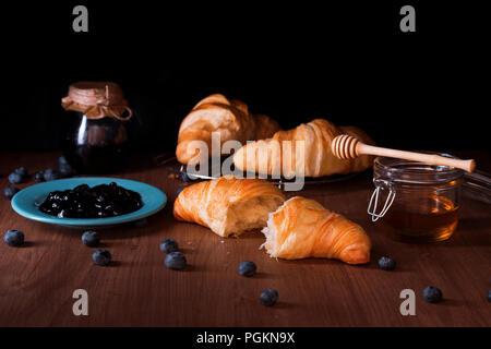 Beurre frais croissants, le verre avec du miel, turquoise plaque avec de la confiture de bleuets, de la confiture de bleuets dans le verre, les bleuets dispersés sur un sol en bois foncé