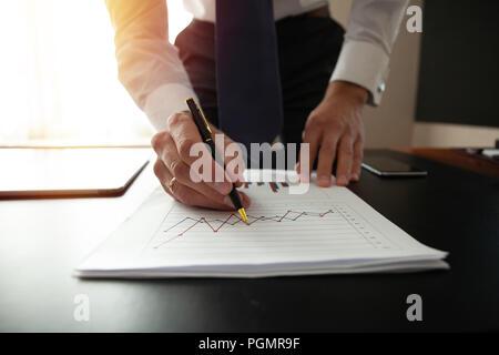 L'analyse des diagrammes de l'investissement d'affaires. Mains de directeur financier en prenant des notes lors de l'utilisation Banque D'Images