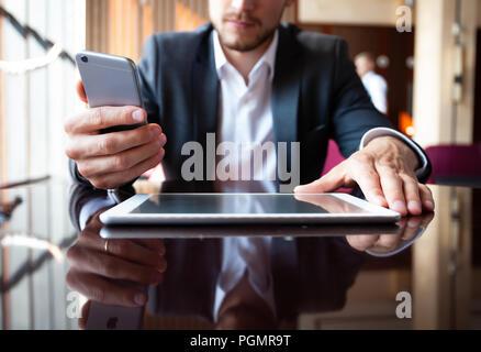 Jeune homme d'affaires travaillant avec les appareils modernes, tablette numérique, ordinateur et téléphone mobile. Banque D'Images