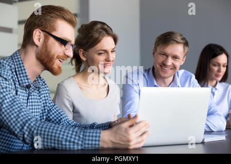 Regarder la vidéo intéressante Smiling workers at laptop in office Banque D'Images