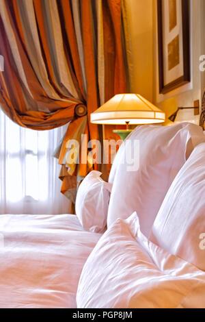 Chambre De luxe Détail montrant un lit king size avec des draps blancs, des oreillers dodus, et de rideaux en soie dans une belle chambre lumineuse. Chic et romantique. Banque D'Images