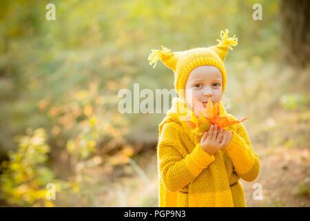 Peu de belle fille blonde avec de grands citrouille en automne fond  Saison  d automne et de personnes concept. Petite fille dans un manteau et un 892cb199e50
