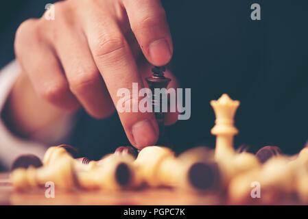 Pièces des échecs sur le conseil. Fond de bois noir derrière.