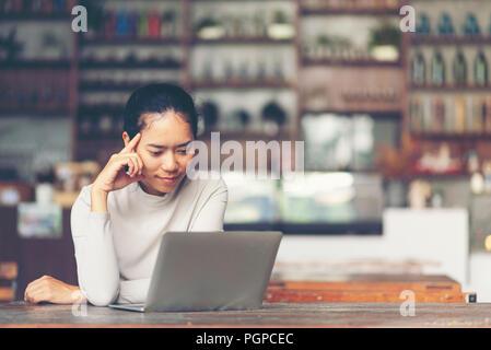 Une belle femme d'âge moyen assis en face de l'ordinateur portable et la gestion de sa petite entreprise à domicile. Banque D'Images