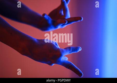 La main de l'homme en rouge et bleu couleur lumière fluorescente Banque D'Images
