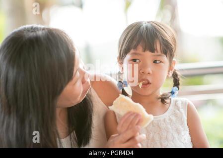L'enfant et de l'alimentation asiatique toast au beurre partage avec maman au café. Vie de famille en plein air avec lumière naturelle. Banque D'Images
