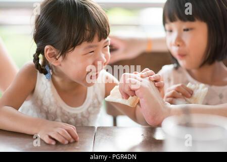 L'alimentation de l'enfant Parent de pain au café. Vie de plein air famille asiatique avec lumière naturelle. Banque D'Images