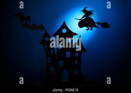 Silhouette château effrayant,papier noir et les chauves-souris sur le balai de sorcière volant sur fond bleu foncé. Halloween concept. Modèle de coupe de papier. Banque D'Images