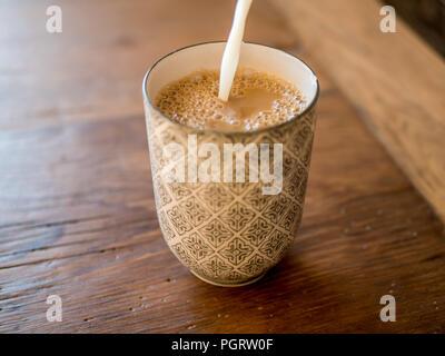 Verser le lait dans la tasse à café ou une tasse. Fokus sélective. Sur la table rustique en bois. Banque D'Images