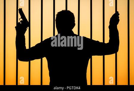 Silhouette of man holding gun regardant à travers les barreaux: concept de droit pour les crimes commis avec des armes à feu, le trafic d'armes/armes, armes à feu, la criminalité des gangs en prison... Banque D'Images