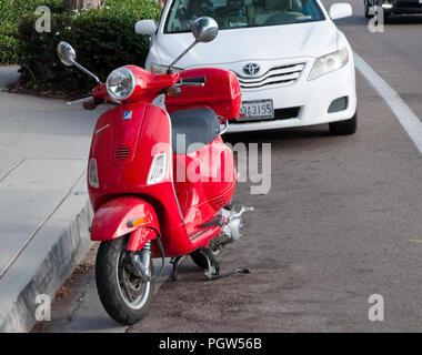 Un scooter Vespa rouge garée devant une voiture blanche dans la rue, à Encinitas, Californie, USA Banque D'Images