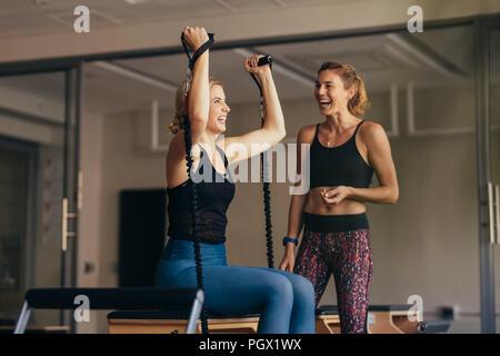 Smiling woman pulling bandes stretch pendant son entraînement pilates. Les femmes à un entraînement pilates gym entraînement tout en faisant rire. Banque D'Images