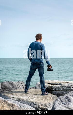 Homme debout sur des rochers surplombant la mer tenant un appareil photo, vue de dos. Banque D'Images