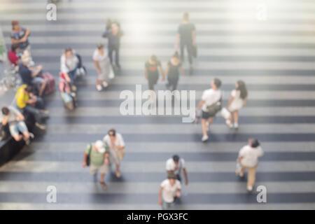 Résumé Les gens marcher brouillée dans terminal de l'aéroport ou gare de salon avec bar d'étage. L'heure d'été, vue d'en haut.