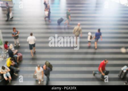 Résumé Les personnes avec bagages marche brouillée dans terminal de l'aéroport ou la gare. L'arrivée et au départ des passagers.