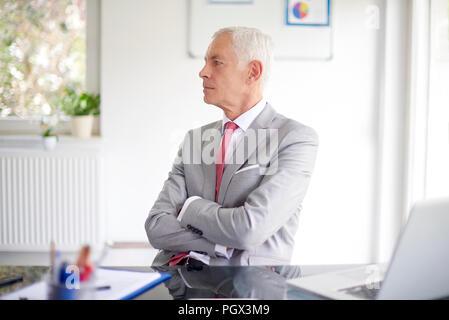 Senior businessman à thougthfully assis à un bureau en face de l'ordinateur portable et de travailler sur de nouveaux projets. Banque D'Images
