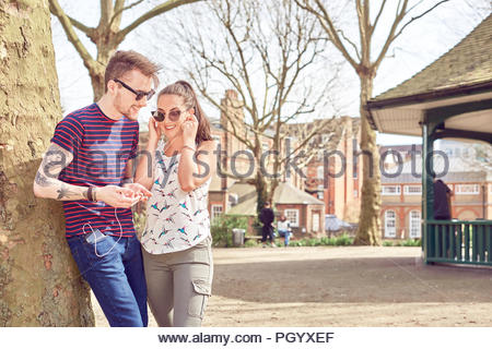 Le partage de la musique couple in park Banque D'Images
