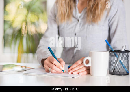 Femme d'affaires écrit dans le document avec le stylo à 24 dans un bureau moderne. Girl shirt porte sur les séquences. Big Green windows floue en arrière-plan Banque D'Images