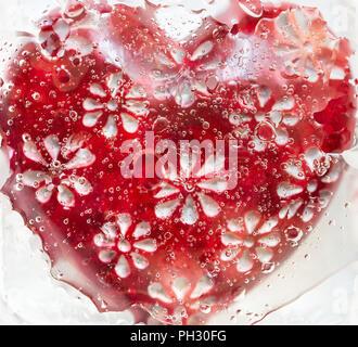 Coeur rouge sous le verre avec de l'eau gouttelettes d'huile et mélanger. Macro Photographie Banque D'Images