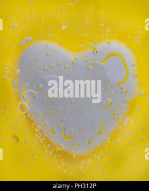 Coeur blanc sous le verre avec de l'eau gouttelettes d'huile et mélanger. Fond jaune. Macro Photographie Banque D'Images