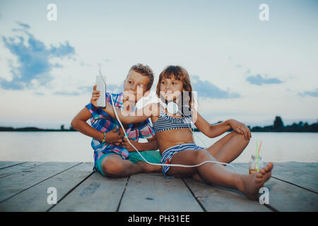 Portrait d'enfants jouant avec des téléphones mobiles ensemble sur une jetée en bois. Décisions. selfies Banque D'Images