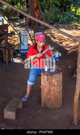 Forgeron local travaillant avec une machette à Houayhe, un village des forgerons dans le Plateau des Bolavens, province de Champasak, au Laos, en Asie du sud-est Banque D'Images
