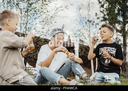 Close up of family blowing bubbles outdoors dans le parc. Banque D'Images
