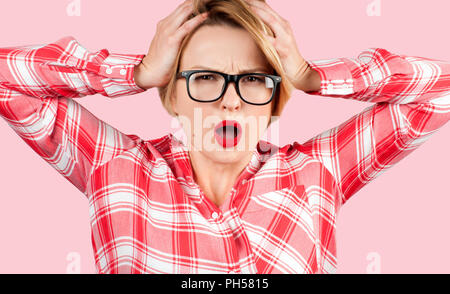 Angry businesswoman touching her head et criant sur fond gris sur fond rose Banque D'Images