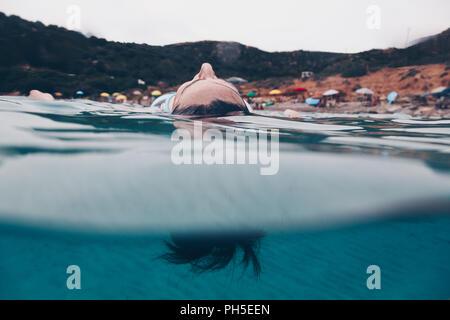 Femme qui reste sur la surface de l'eau avec ses yeux fermés - Détente et méditation concept. Banque D'Images