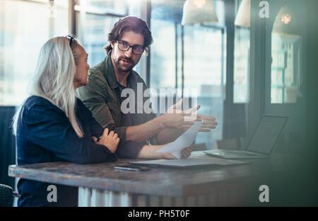 Jeune homme pour expliquer son idée d'entreprise à des femelles matures collègue au travail. Les gens d'affaires ayant une réunion pour discuter du projet. Banque D'Images