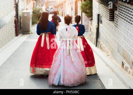 Retour de trois femme portant hanbok marcher dans les maisons de style traditionnel, le village de Bukchon Hanok à Séoul, Corée du Sud. Banque D'Images
