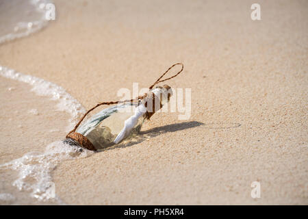Lettre message dans une bouteille transparente en verre sur la plage , concept pour la communication. Banque D'Images